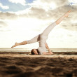 Young beautiful slim woman practices yoga on the beach at sunris — Stock Photo #46340969