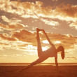 Young beautiful slim woman silhouette practices yoga on the beac — Stock Photo