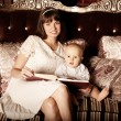 Mother with a small child in the interior reading a book togethe — Stock Photo #46348849