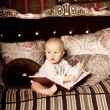 Small child in the interior reading a book. Smiling baby in the — Stock Photo #46348853