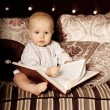 Small child in the interior reading a book. Smiling baby in the — Stock Photo #46348863