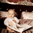 Small child in the interior reading a book. Smiling baby in the — Stock Photo #46348915