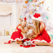 Mom and daughter dressed as Santa celebrate Christmas. Family at — Stock Photo #46349919