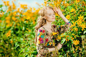 Young beautiful smiling woman in the blooming garden with flower — Stock Photo