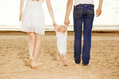 First steps of the kid. Happy family is helping baby takes first — Stock Photo