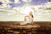 Young beautiful slim woman practices yoga on the beach at sunset — Stock Photo