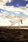 Young beautiful slim woman practices yoga on the beach at sunris — Stock Photo