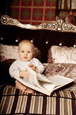 Small child in the interior reading a book. Smiling baby in the  — Stockfoto