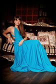 Beautiful woman in a long blue dress in the rich interior. Young — Stock Photo
