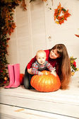 Beautiful woman with a child on the front porch with pumpkins au — Stock Photo
