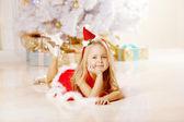 Krásná santa holčička u vánočního stromu. šťastná dívka — Stock fotografie