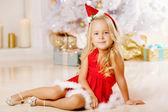 Beautiful little Santa girl near the Christmas tree.  Happy girl — Stock Photo
