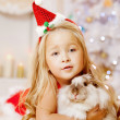 Beautiful little Santa girl near the Christmas tree. Happy girl — Stock Photo #46350023