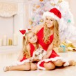 Mother and daughter dressed as Santa celebrate Christmas. Family — Stock Photo