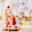 Beautiful little Santa girl near the Christmas tree. Happy girl — Stock Photo