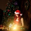Young beautiful smiling santa woman near the Christmas tree with — Stock Photo #46350287