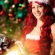Young beautiful smiling santa woman near the Christmas tree with — Stock Photo