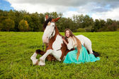 Beautiful woman with a horse in the field. Girl on a farm with a — Photo