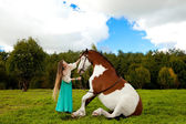 Beautiful woman with a horse in the field. Girl on a farm with a — Стоковое фото