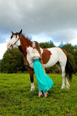 Beautiful woman with a horse in the field. Girl on a farm with a — Foto Stock