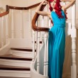 Young woman with luxurious long beautiful red hair in a blue fas — 图库照片