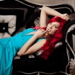 Young woman with luxurious long beautiful red hair in a blue fas — Стоковое фото