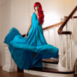 Young woman with luxurious long beautiful red hair in a blue fas — Stok fotoğraf #48564213
