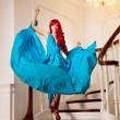 Young woman with luxurious long beautiful red hair in a blue fas — Stok fotoğraf #48564243