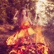 Beautiful witch in the woods near the fire. Magic woman celebrat — Stock Photo #48564345