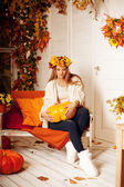 Beautiful autumn woman smiling on the porch of yellow and orange — Stock Photo