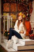 Beauty autumn woman smiling on the porch of yellow and orange au — Stock Photo