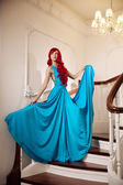 Young woman with luxurious long beautiful red hair in a blue fas — Stock Photo