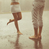A loving young couple hugging and kissing under a rain. Lovers m — Stock Photo