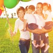 Happy family holding colorful balloons. Mom, ded and two daughte — Stock Photo #51085175