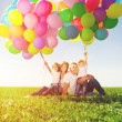 Happy family holding colorful balloons. Mom, ded and two daughte — Stock Photo #51085181