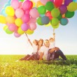 Happy family holding colorful balloons. Mom, ded and two daughte — Stock Photo