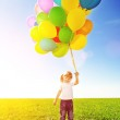 Little girl holding colorful balloons. Child playing on a green — Stock Photo #51085189