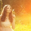 Beautiful young woman blowing a dandelion. Trendy young girl at — Stock Photo #51085455
