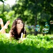 Woman and soap bubbles in park. Beautiful young girl lying on th — Foto Stock