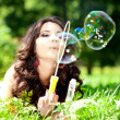 Woman and soap bubbles in park. Beautiful young girl lying on th — Стоковое фото