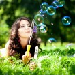 Woman and soap bubbles in park. Beautiful young girl lying on th — Stok fotoğraf