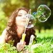 Woman and soap bubbles in park. Beautiful young girl lying on th — Stok fotoğraf #51086699