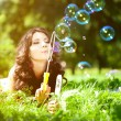 Woman and soap bubbles in park. Beautiful young girl lying on th — Photo