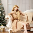 Luxury blonde in interior New Year. Young beauty trendy girl cel — Stock Photo