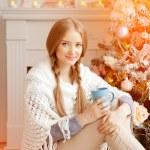 Beautiful young woman drinking tea at the Christmas tree. Beauti — Stock Photo #51087605
