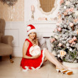 Young beautiful smiling santa woman near the Christmas tree. Fas — Stock Photo #51087647