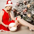 Young beautiful smiling santa woman near the Christmas tree. Fas — Stock Photo #51087681