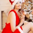 Young beautiful smiling santa woman near the Christmas tree. Fas — Stock Photo #51087687
