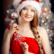 Young beautiful smiling santa woman near the Christmas tree. Fas — Stock Photo #51087699