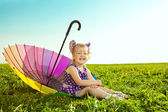 Beautiful little girl with rainbow umbrella on the grass in the  — Stockfoto
